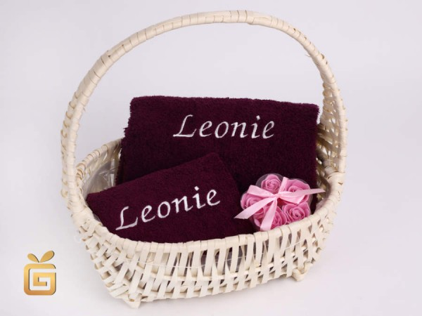 Besticktes Handtuch im Geschenkkorb mit Baderosen